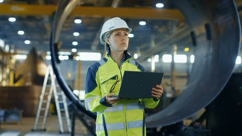 Female Industrial Engineer in the Hard Hat Uses Laptop Computer while Standing in the Heavy Industry Manufacturing Factory. In the Background Various Metalwork Project Parts Lying. 4K UHD.