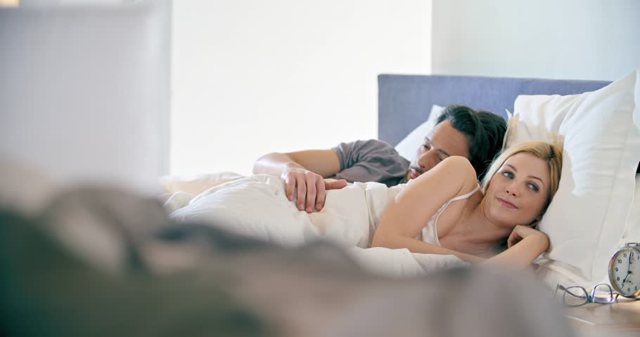 Blonde woman and man smiling, standing up. Couple in love morning wake up at home in bedroom. Caucasian girlfriend and boyfriend people liying on bed. Lovely strokes. 4k video