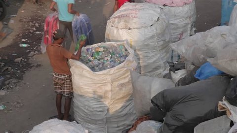 A man packing segregated plastic bottles for recycling in a huge sack in the slums, Dharavi, Mumbai, India (2017)