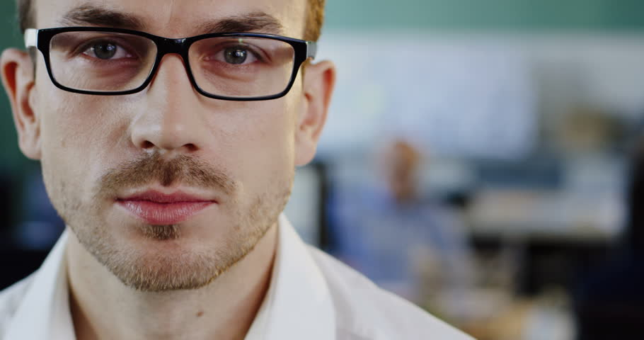 Close up of Caucasian attractive young man in glasses looking and starting to smile sincerely into the camera. The blurred office space background. Portrait shot. Indoor