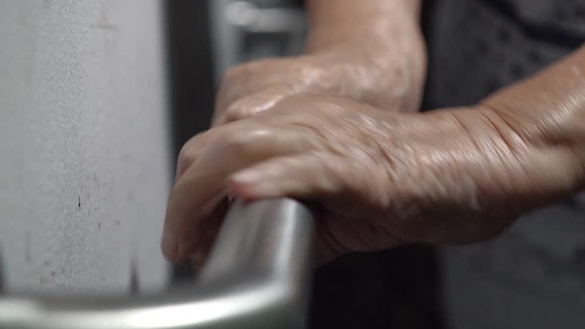 Elderly woman holding on handrail for support walking | Shutterstock HD Video #32858026