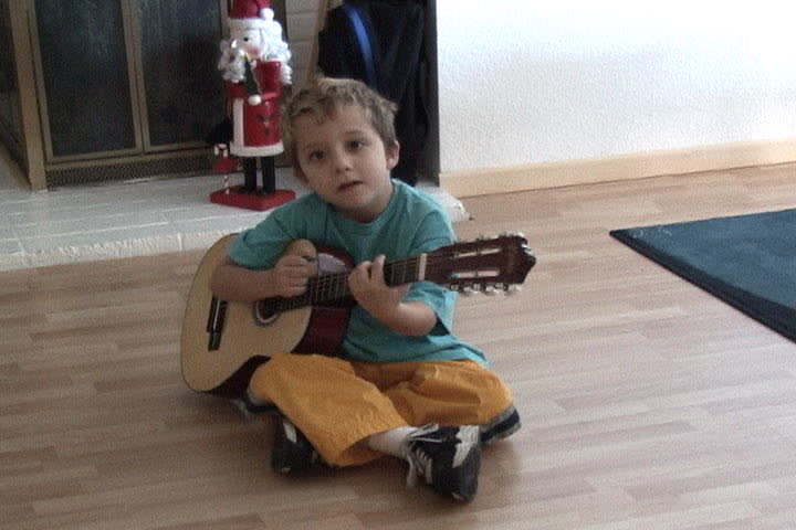 Young boy plays on guitar as practice for being a Future Rock star