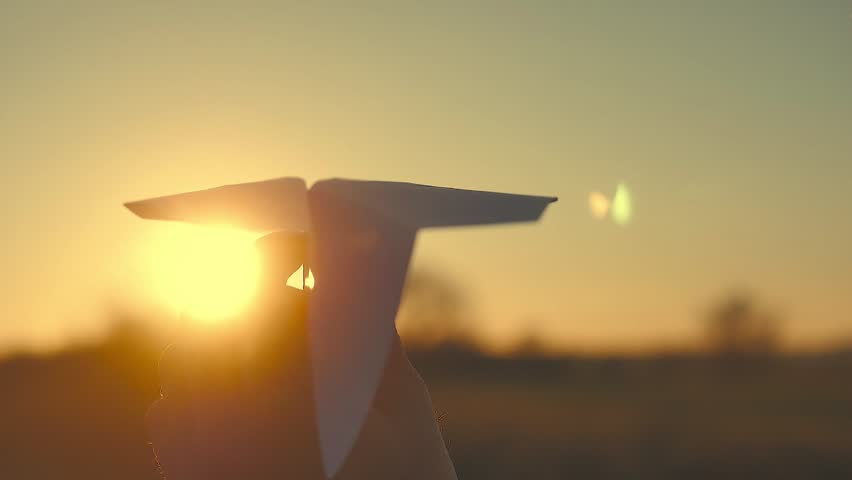 The man hold paper airplane on the background of picturesque sunset.  | Shutterstock HD Video #32946526