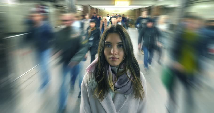 Beautiful young woman standing alone in moving crowd, looking at camera. 4K UHD timelapse. | Shutterstock HD Video #32965006