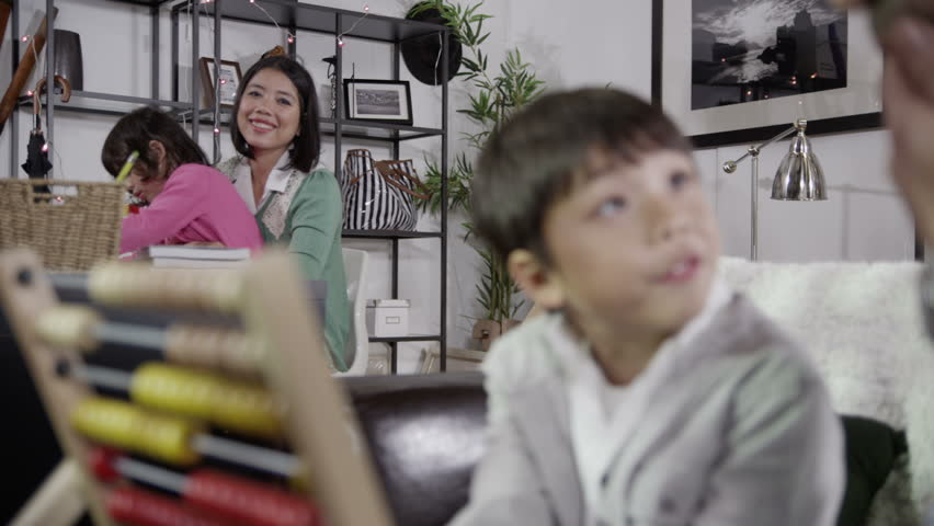 Happy family spending time together at home. Mother and father are helping their children to learn. In slow motion | Shutterstock HD Video #3299831