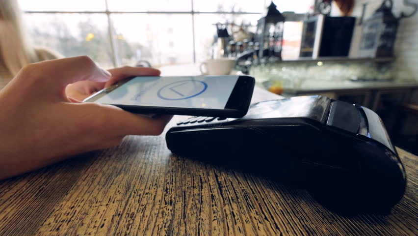 Close-up customer hand uses smartphone to make a wireless payment.