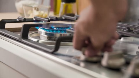 Advanced gas stove with automatic electric ignition. Chef turns the knob top valvet on and puts on wok to prepare healthy and tasty dish.