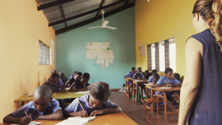 4k of African students write english alphabet in notebooks in school classroom.