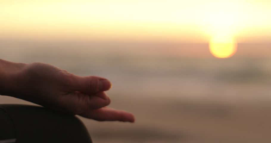 Female fingers in Chin mudra hand position lying on knee at sea sunset background close up detail 4k. Yoga woman in meditation. Concentrating on wisdom and inner peace. Relaxation and meditative state | Shutterstock HD Video #33012976