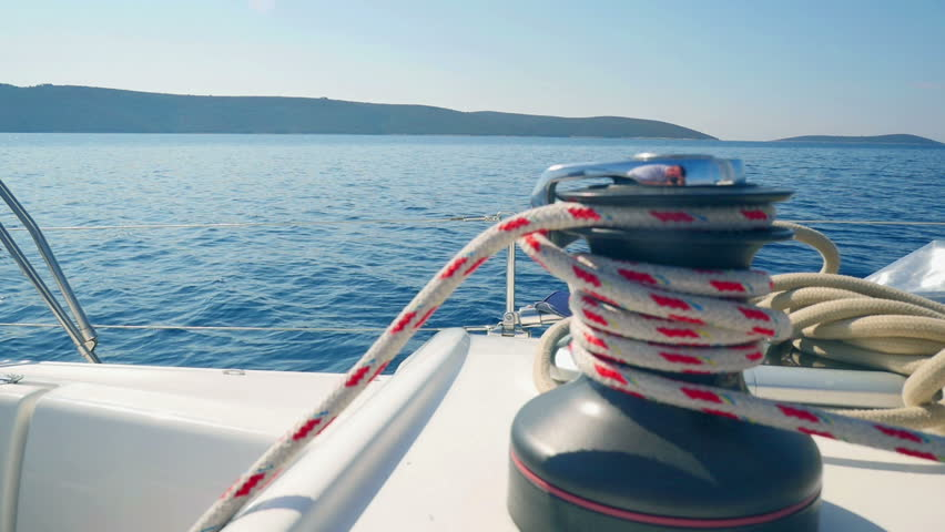 White and red colored rope winded on sailings boat main winch. Sailing boat slowly moving in soft wind with beautiful sunny day in background. Filmed in slow motion hd.