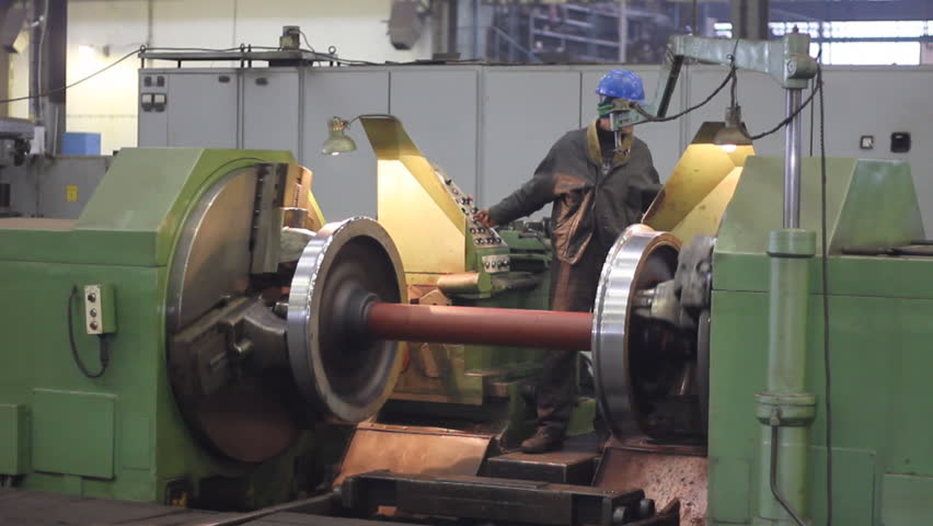 Worker on a machine, metal working lathe a in factory. Machining process in the factory for repair of trains and wagons