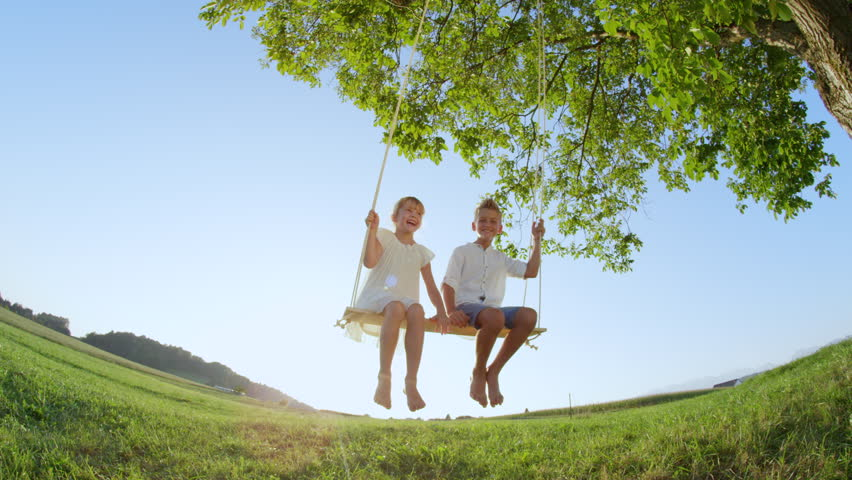 SLOW MOTION LOW ANGLE Smiling boy and girl having fun swaying on a wooden swing under a big green tree. Happy couple of young kids swinging on a timber swing set. Siblings enjoying summer on a swing