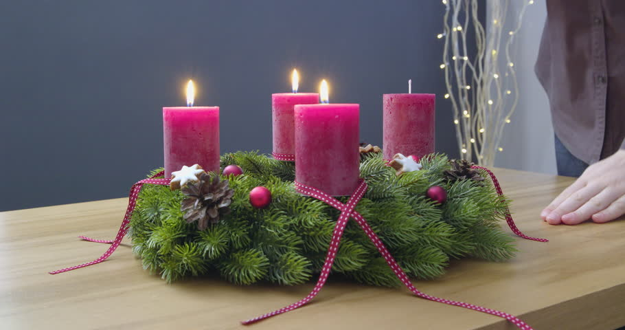 Fourth Sunday of Advent - a young woman is lighting the fourth candle of the advent wreath - ProRes