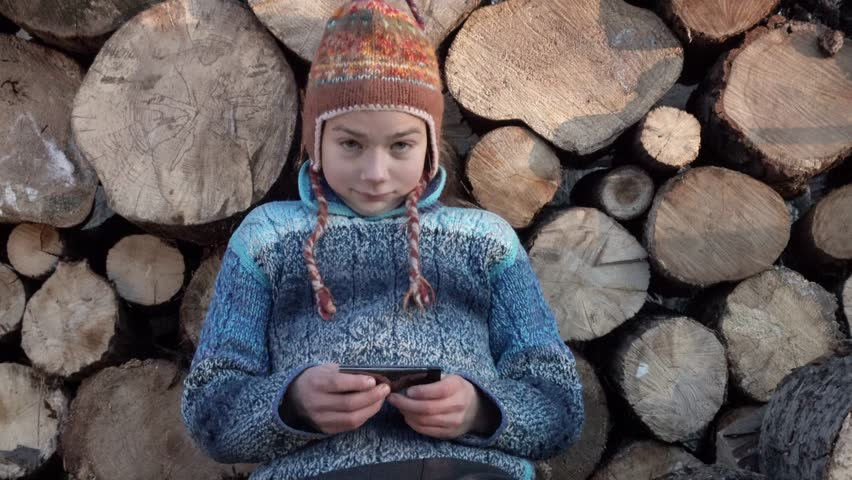 The boy is playing on the smartphone and hiding it behind his back. Portrait of a child on the background of firewood playing on a smartphone.  | Shutterstock HD Video #33094123