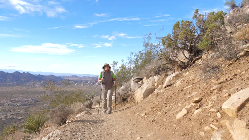A female tourist with a backpack and sun-protective clothes, she walks along a mountain trail up the hill, uses trekking poles. Front view, slow motion. Joshua Tree National Park, California, America.