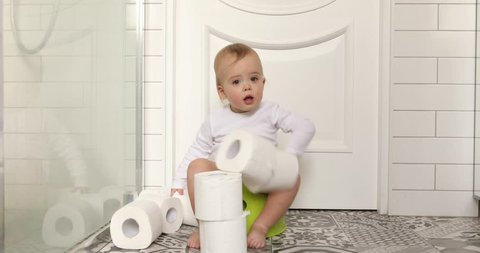 Funny baby boy sitting on chamberpot, Children's legs hanging down from a chamber-pot. Kid plays toilet paper
