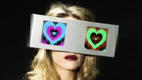 head of a woman looking around with 2 video screens as eyes. the screens have a hypnotic video of hearts on them with data code overlayed. all content is from my own collection