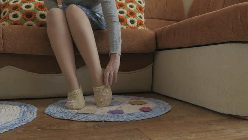 3b7f4eac005bb Woman's feet wearing warm knitted slippers. Braided rug