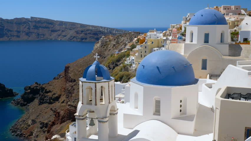 Panning view of blue dome churches and Caldera in Santorini Island, Greece. Aegean Sea