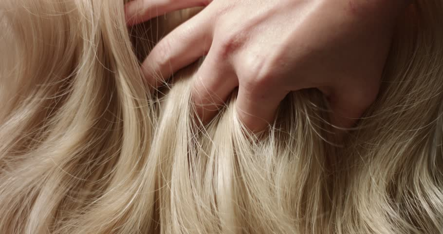 A woman's hand with bright manicure running through long wavy blond hair | Shutterstock HD Video #33165886