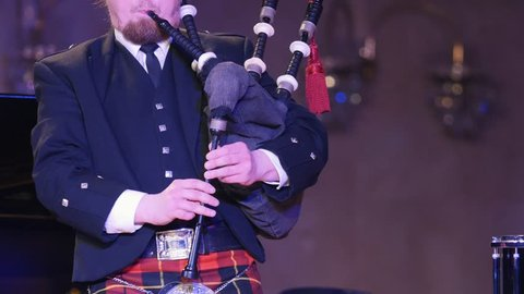 Bagpipe player in a kilt plays musical instrument at the stage