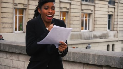 Actress got dream role in feature film. Happy African American with scenario in hands standing on street in big city and dancing. Young woman with black curly hair and bang wearing black jacket and