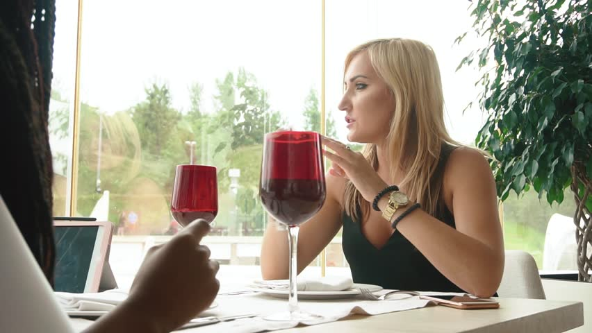Two women drinking wine from wineglasses on informal meeting in resturant. Focus on blonde woman