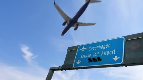 airplane flying over copenhagen airport signboard