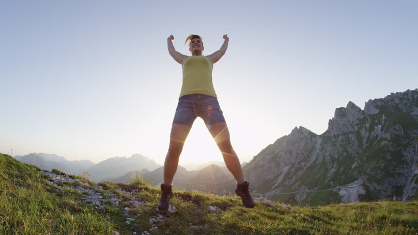 SLOW MOTION LENS FLARE: Cheerful young woman jumping high into air, celebrating mountain ascent. Happy female hiker jumping and outstretching arms after reaching mountaintop. Sports girl on trekking