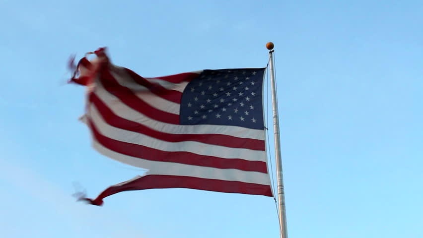 A torn and tattered American flag waves in the wind