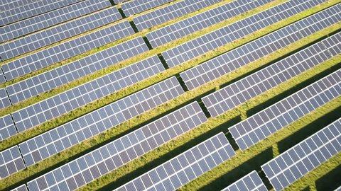 Solar panels and renewable energy farm. Aerial drone video footage looking down onto rows of solar panels in a renewable energy farm in the English countryside in bright dusky sunshine.