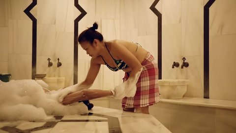 young woman is lying in a hammam face up, is covered by soap foam, masseur is doing massage