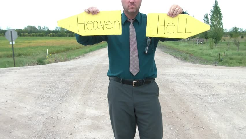 Business guy holds up pointed yellow signs on dirt road intersection reading heaven in one hand and hell in the other.