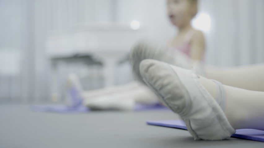 A close up of girl feet in gymshoes while doing the swing sideward during the ballet class. The little dancer sits on the flour and her friend is rightward. The children turns their left legs left | Shutterstock HD Video #33260446