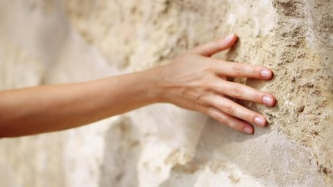 Woman's hand moving over old stone wall. Sliding along. Sensual touching. Hard stone surface. Sensory experience