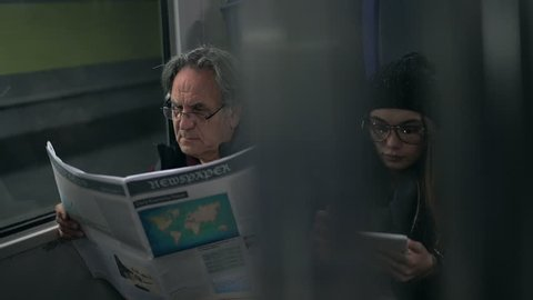 Passengers reading newspaper with using tablet in the metro