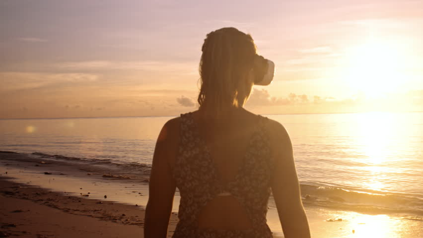4k imagination concept of woman on coastline wearing virtual reality headset enjoying sunrise with sun flare, watching 360 video experiance. | Shutterstock HD Video #33287176
