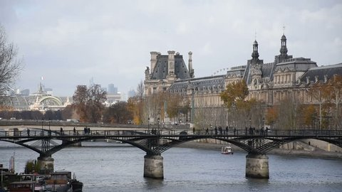 """Paris, People walking on """"Pont des Arts"""" on the Seine River in front of the Louvre Museum, France"""