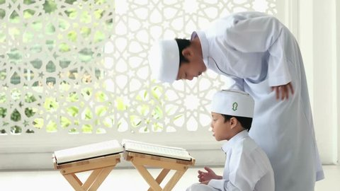 Two young boys reading Quran together in a mosque