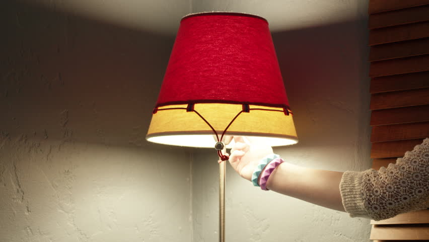 Closeup of a red and yellow lamp being turned off by a female arm #33310276
