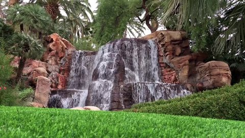 A lush waterfall surrounded by fresh cut grass