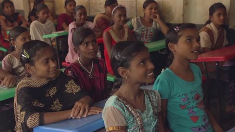 School girls sitting in a classroom are smiling and replying to a teachers questions in Chandrapur, Maharashtra, India (2017)