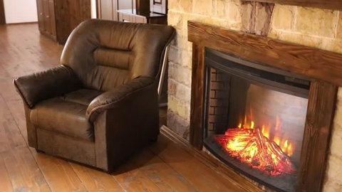 Leather armchair and fireplace with artificial fire in the living room