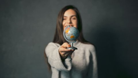 Beautiful dark-haired girl in warm grey sweater turning the globe, indoor isolated shot