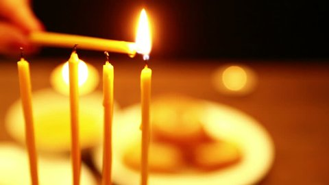 a woman holds a candle in her hand with the help of which she lights candles of Hanukkah. a woman lights candles from the first candle from right to left. close-up. the camera moves from right to left