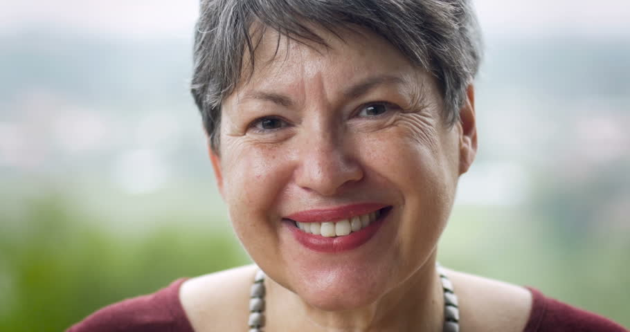 Attractive mature woman in her 60s with short hair smiling for the camera