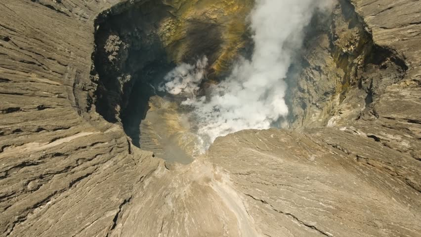 Inside the active volcano crater, white smoke. Aerial view of volcano crater Mount Gunung Bromo is an active volcano,Tengger Semeru National Park. 4K video. Aerial footage.
