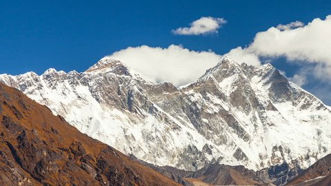 Mount Everest epic aerial wide shot panoramic view of snowcapped cold rocky mountains with clouds in Nepal near tibet with cloudy skies and fierce winds