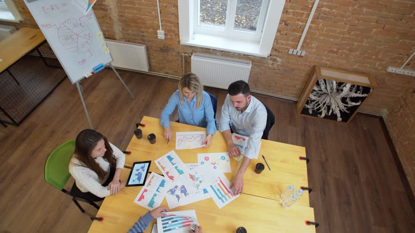 Business meeting at loft shared space. Team talking, woman manager giving direction to people. Top view. | Shutterstock HD Video #33387229
