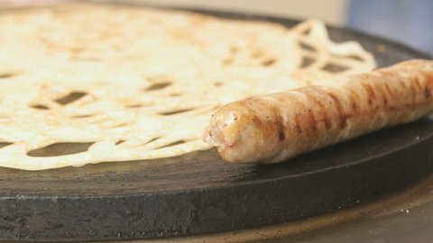 Process of cooking traditional russian pancake with sausage on a electric tile. Close-up of hot dog